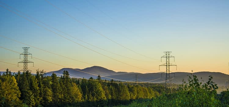 power lines over a landscape of forest and distant hills