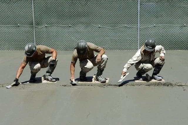 three cement masons with matching helmets smoothing cement together